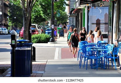Wilmington, NC/USA- 06/24/2018: Attractive young women walk along Wilmington's historic Front Street on a hot afternoon.