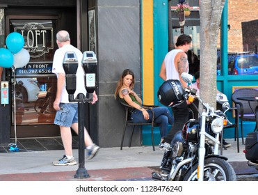 Wilmington, NC/USA- 06/24/2018: A beautiful young woman shows off a fresh tattoo in front of a downtown cafe.