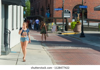 Wilmington, NC/USA- 06/24/2018: Two young women walk along Wilmington's historic Front Street on a hot afternoon.