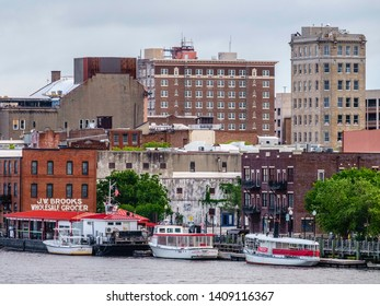 WILMINGTON, NC/USA - MAY 12, 2019: Three small tour boats wait near historic warehouse J.W. Brooks Wholesale Grocer by the Wilmington Downtown Riverwalk along Cape Fear River on a Sunday morning.