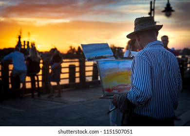 WILMINGTON, NORTH CAROLINA - 4 AUGUST 2018: A man paints a picture of the sunset along the Cape Fear River