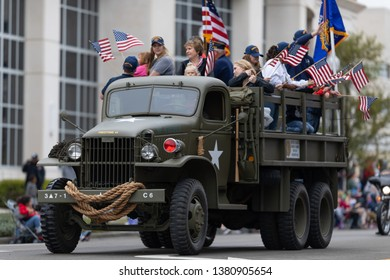 Wilmington, North Carolina, USA - April 6, 2019: The North CarolinaAzalea Festival, GMC CCKW World War 2 Truck, carrying people down 3rd street with american flags at the parade