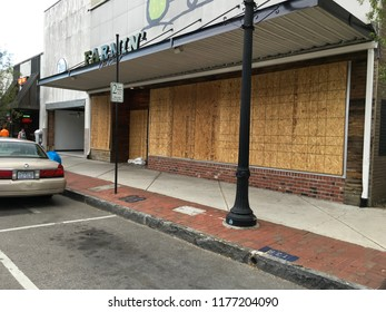 Wilmington North Carolina - USA / September 11, 2018. Downtown businesses boarding up for Hurricane Florence. Farmin' store boarded up for Hurricane Florence