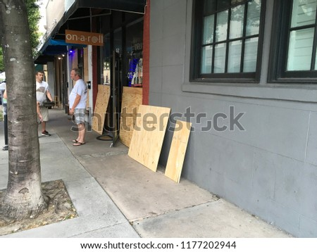 Wilmington North Carolina - USA / September 11, 2018. Downtown businesses boarding up for Hurricane Florence. ON A Roll boarding up windows for Hurricane Florence