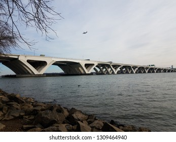 Wilson bridge and Potomac river with rocks and shore and airplane