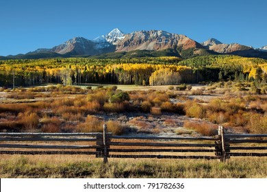 Wilson Peak in the Colorado Rockies near Telluride with yellow and green aspens and rail fence just after sunrise