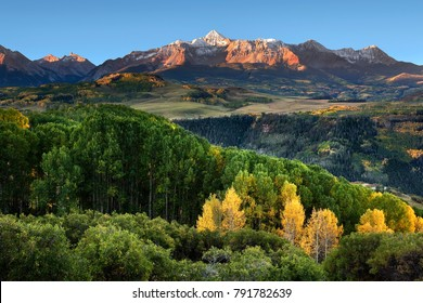 Wilson Peak in the Colorado Rockies near Telluride with a stand of yellow aspens and rolling hills in the distance just after dawn