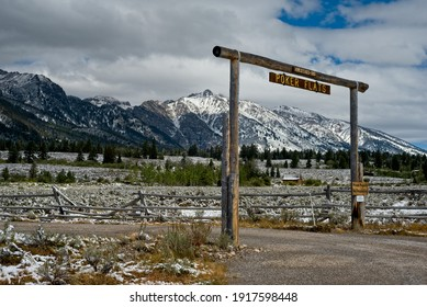 WILSON, WY, USA - SEPTEMBER 8, 2020: The picturesque entrance sign to the Poker Flats ranch rises above the Teton range just inside Grand Teton National Park on a snow-dusted, cold morning.
