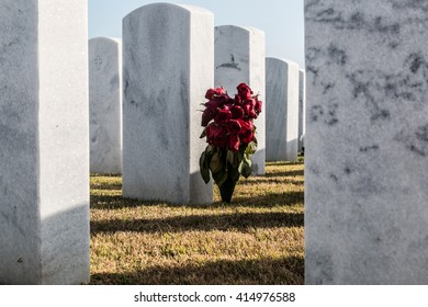 Wilted rose bouquet and tombstones at Miramar National Cemetery in San Diego, California.