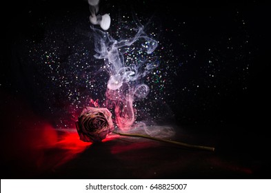 A wilting rose signifies lost love, divorce, or a bad relationship, dead rose on dark background with smoke