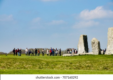 Wiltshire, England - April 7, 2017: Tourists and some huge standing stones of Stonehenge with green grassland in foreground on a sunny day with bright blue sky in horizontal view.