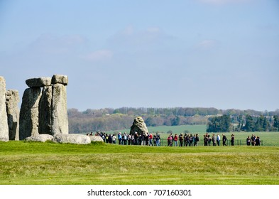 Wiltshire, England - April 7, 2017: Tourists and some huge standing stones of Stonehenge with green grassland in foreground on a sunny day in horizontal view.