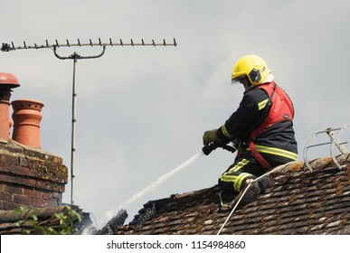 Wiltshire, UK. August 13 2018. A firefighter on a roof tackling a residential house fire