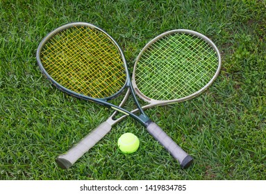 Wimbledon sign, two tennis rackets with a ball on grass