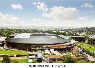Wimbledon stadium under sunny blue sky day with green trees and parks around London skyline in horizon