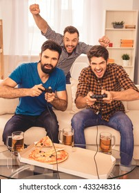 Its a win! excited happy cheerful men play video game with beer and pizza