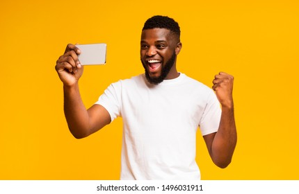 Win Game. Excited African Guy Celebrating Success, Using Smartphone over Yellow Background, Copy Space