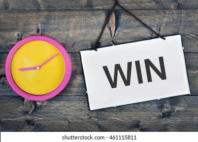 Win sign and clock on wooden table