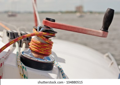 winch handle inserted into large winch with red and yellow line wrapped