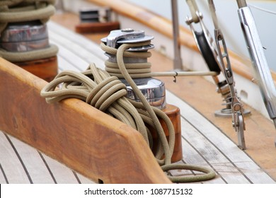 Winch and rope on an old wooden sailboat yacht with teak and pulleys close up detail
