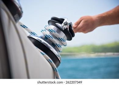 Winch and sailors hands on a sailboat. Shot with a selective focus