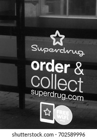 Winchester, Hampshire, England - August 14, 2017: Monochrome Superdrug store click and collect sign in shop window, United Kingdom based health and beauty retailer