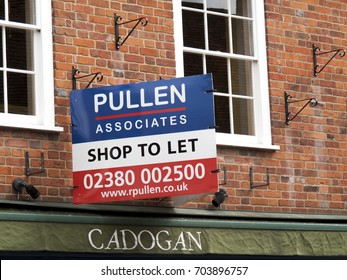 Winchester, Hampshire, England - August 14, 2017: Pullen Associates shop to let advertising sign over vacant retail premises