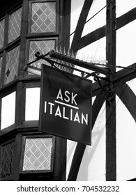 Winchester, Hampshire, England - August 14, 2017: Monochrome Ask Italian coffee shop and restaurant sign over premises, company founded by brothers Adam and Samuel Kaye in 1993