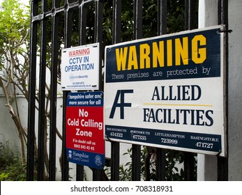 Winchester, Hampshire, England - August 14, 2017: Allied Facilities these premises are protected warning sign mounted on iron gates, entrance to industrial estate