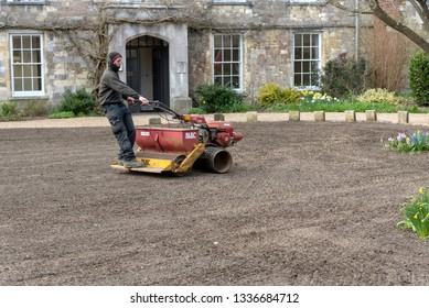 Winchester, Hampshire, England UK. March 2019. Landscape gardener riding on a seed spreader and roller to form a new lawn.