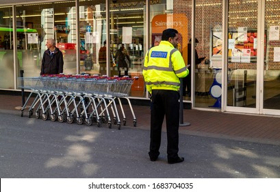 Winchester, Hampshire, England, UK, March 2020. Security officer outside a Winchester supermarket. Allowing only one customer to enter at a time during Coronavirus epidemic.