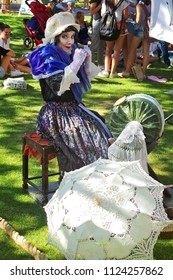 WINCHESTER HAT FAIR HAMPSHIRE ENGLAND UK – 30 JUNE 2018 – A mime artist from The Clamours of Paris depicts The Lacemaker, amusing crowds in Abbey Gardens during the annual Hat Fair