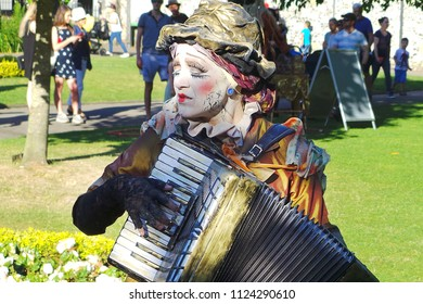 WINCHESTER HAT FAIR HAMPSHIRE ENGLAND UK – 30 JUNE 2018 – Artist from The Clamours of Paris mimes The Singer, along with her accordion, in Abbey Gardens during the annual Hat Fair