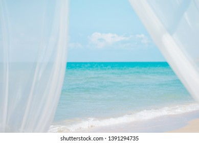 Wind blow white curtains on sand sea,summer holiday concept.