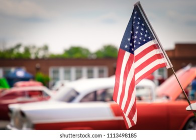 The wind blowing an American flag over a classic American fifties car at a Virginia show.
