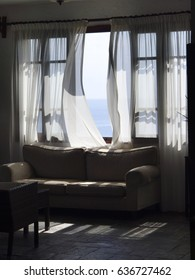 Wind blowing through window waving curtain for view to sea