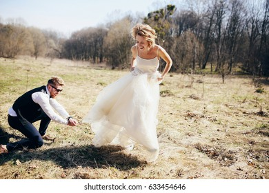 Wind blows bride's dress while she poses with groom on the lawn