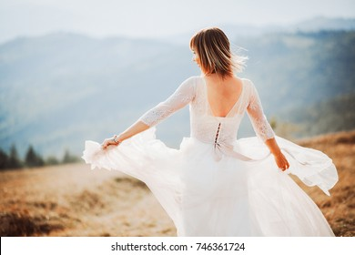 Wind blows bride's hair and dress while she poses on the mountain hill