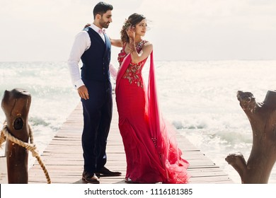 Wind blows bride's pink sari while she stands with Hindu groom on a wooden quay among foaming waves