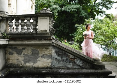 Wind blows dress of gorgeous bride while she stands on ruined stairs