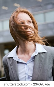 Wind blows the hair of a young business woman in a gray suit, standing before an office building.