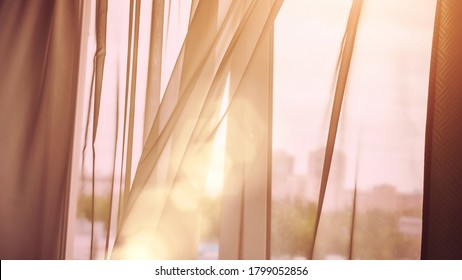 wind blows off transparent room curtain against blurry cityscape silhouette at back orange morning sunlight close view