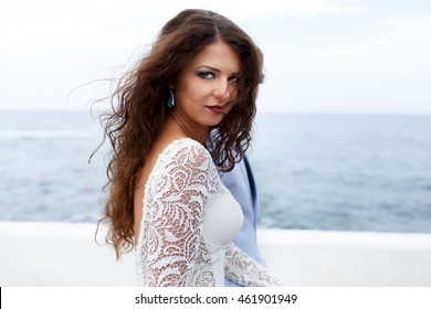 Wind blows seductive bride's curls while she walks by the sea