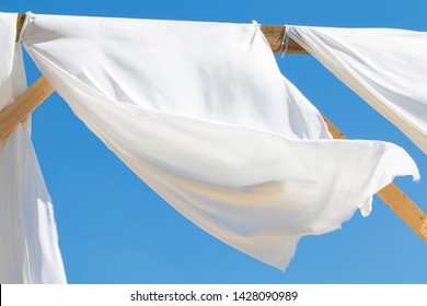 the wind blows white awnings, on the seashore against the blue sky