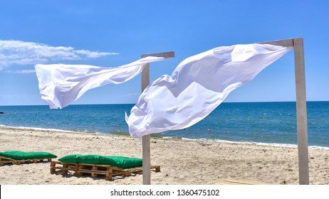 wind blows white canopy curtains, on the seashore