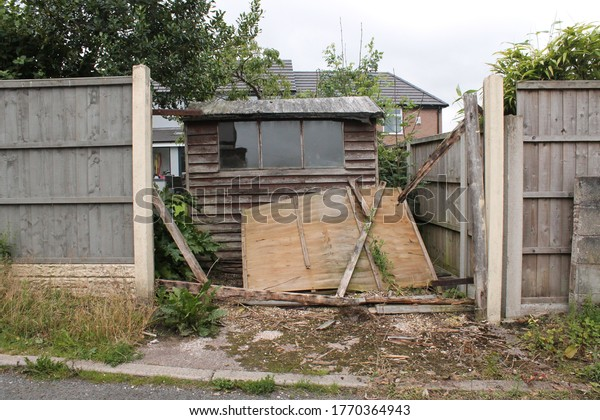 wind damage fence panel at the back of a garden, revealing a ram shackled shed