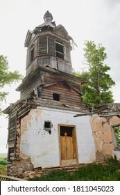 Wind damaged country church shows broken steeple. Exposed roofline has broken boards.