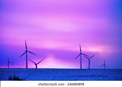 wind driven electric plant in firstlight on snow
