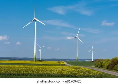 Wind energy in a blooming rapeseed field seen in rural Germany