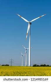 Wind energy plants in a field of blooming oilseed rape seen in Germany